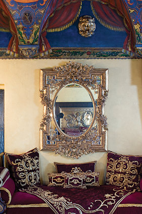 An exquisite antique Italian gilt mirror hangs above a recamier with velvet and gold embroidered pillows.