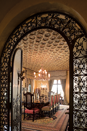 Doors of wrought iron and frosted glass, original to the house, lead into the dining room. Arranged around the table are Spanish-style chairs from the 1920s. A pair of seventeenth-century period Spanish chairs, restored and upholstered with embossed leather, are also in the room, though not illustrated.