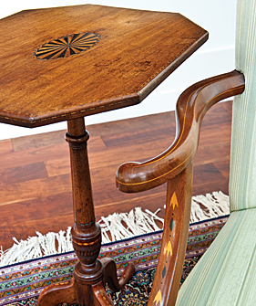 Detail of the inlay and craftsmanship on a candlestand and lolling chair in the east end of the great room.