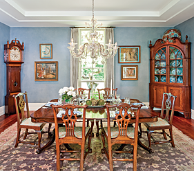 "The formal dining room has a mix of both Chippendale and Federal furniture. The double-pedestal mahogany dining table from New York is surrounded by a set of six Boston or Salem Chippendale mahogany chairs, circa 1760. The scrolled top corner cupboard, probably from the mid-Atlantic states, is one of the wife's favorite pieces. It is enhanced with burl and satinwood, inlay, carved sunflower rosettes, and finials carved to resemble pine cones. Retaining all of its original glass and its original surface, it is both functional and very dramatic. The eight-day, brass movement tall clock in the other corner of the dining room plays seven songs. It is among the husband's favorite pieces—combining his interests in provenance, inlay, and mechanical complexity. Made of cherry and figured maple in 1817, it is one of only three clocks by Asa Munger of Herkimer, N.Y., and descended in his daughter's family.   Complementing the furniture is a group of four schoolgirl embroideries with classical themes, stitched and painted at Boston schools in the early nineteenth century. Two show scenes from Shakespeare's The Tempest and Cymbeline (lower left, upper right). Work from the Saunders and Beach Academy are represented on the upper left with ""the Monarch and the Butterfly"" and on the lower right ""elemachus and Mentor on the Island of Calypso."""