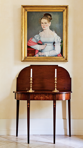 "Some of the pieces of most importance to the collectors are displayed in the foyer. A Federal card table, probably made in or near Providence, R.I, circa 1800, is one of the finest examples of the form. Above it is a portrait of Kate Elting, painted in New Paltz, New York, probably in 1824. The sitter's white dress shows the artist's ability to adroitly picture transparent fabric. Kate leans on the edge of a table that is still in the Elting family house in New Paltz, now owned by the Huguenot Society, and in which portraits of other members of her family still hang. The original gilded leaf and berry frame is labeled by its maker, ""Bernard/Carver, Gilder, and Looking—Glass Manufactgurer/1-2 Warren Street (New York City);"" the firm was at this location only in 1824."