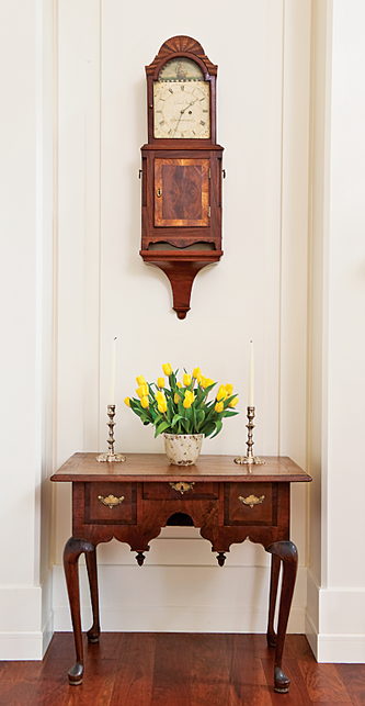"""Set off in a corner of the great room is a rare, small, veneered maple Queen Anne dressing table, measuring only 28-1/2 inches wide. This piece was probably made in the Hartford, Conn., area, circa 1740. A nearly identical example is shown in Connecticut Valley Furniture, Kugelman and Lionetti (2005). Above the dressing table is an exceptional mahogany shelf clock signed """"David Wood of Newburyport."""" The interior door of this circa 1805 Massachusetts clock retains his label """"David Wood Watch and Clockmaker Newburyport."""" A similar clock is in the Department of State collection, as seen in Treasures of State, Conger and Rollins (1991)."""