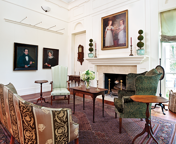 """The focal point of the east end of the great room is the Newport tea table made of choice mahogany, which descended in the Morris family of Philadelphia and was found covered with years of accumulated dirt in one of the family's barns. The Federal sofa, with rounded ends is a delicate example of the form. The wing chair, with dramatically shaped wings and bell-flower inlaid legs, is from Portsmouth, N.H., circa 1790-1800. The lolling chair, with an equally tall back, has remarkable inlaid and """"scooped"""" arms, bell flower and dot inlays on the arm supports, and was probably made in the Concord, N.H., area, possibly by George Rogers. The mahogany candle stand beside the lolling chair, one of several inlaid examples in the collection, is a tour de force of """"high country"""" work; its combination of form and ornamentation reflects the best of New England Federal period furniture. The initials """"EB"""" are inlaid on the top of the block under the tilting top. The pieces in this room view illustrate the union of the collectors' interest in furniture and painting, representing, as the husband says, """"their awareness that one should be a complement to the other because they share a similar aesthetic.""""  Above the fireplace at the east end of the room hangs the double portrait of the Davis children, Eliza Cheever Davis and John Derby Davis, painted in Boston circa 1795 by Edward Savage (1761-1817). This painting measures a commanding fifty-four inches in height and is in its original gilded neoclassical frame. It is a fine example of Federal portraiture of children and one of Savage's most intimate paintings.   The great room also contains two Phillips portraits from the 1835-1840 period. One is of Elizabeth Mygans. The painting's dark background and its original dark painted frame contribute to making this a beautiful and sensitive portrait of this young woman. Like the portrait of Helen Lena Ten Broeck, over the mantel in the west end of the room, this painting projects the sitter's"""