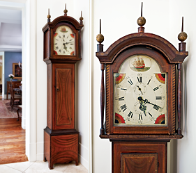 In a corner of the kitchen is a small wooden works clock with a wonderful dry grain-painted surface. The brightly-painted dial is centered by a three-masted ship, and the free-hand decoration simulating inlay on the hood is exceptional. Leaves, diamonds, circles, vines, flowers, and garlands are detailed in white, yellow, orange, red, and black. The Greek key inlay banding on the case door is painted in gold, as are the brass finials. This minutely detailed decoration stands in contrast with the broad swaths of grained paint on the case. With a chestnut backboard and old repair labels from two towns in Rhode Island, this clock was probably made there in circa 1815-1820.