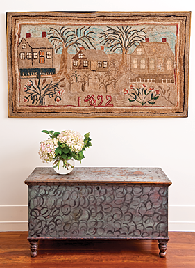 Within the master bedroom, a blue-painted Pennsylvania blanket chest, with whimsically enhanced black swirls, scallop, and dot decoration, sits beneath a large New England hooked rug, dated 1892.