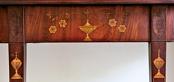 The quality of the inlay work on this Rhode Island card table in the foyer is matched by the original finish and condition. The covered urns on the legs, rather than on the plinths, which are composed of grained mahogany, are an unusual and attractive treatment.