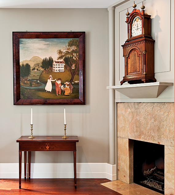 The large painting above the card table, by an unidentified artist, at the fireplace end of the husband's study is an early example of a fully developed folk art landscape painting, circa 1810-1820. Below the painting is a rare Federal card table attributed to Nathan Lombard of Sutton, Mass. (A table of similar form is in the Garvin collection at Yale.) The shelf clock on the mantel is signed by John Bailey of Hanover, Mass, and the rear of the moon-phase dial is signed J. Minott 1793, regarded as one of the best Federal-era dial painters. Made to appear as a clock sitting on a separate base, both sections have brass, stop-fluted columns, ogee bases, and the lower case features an applied scrolled molding and deeply-carved paneled door.