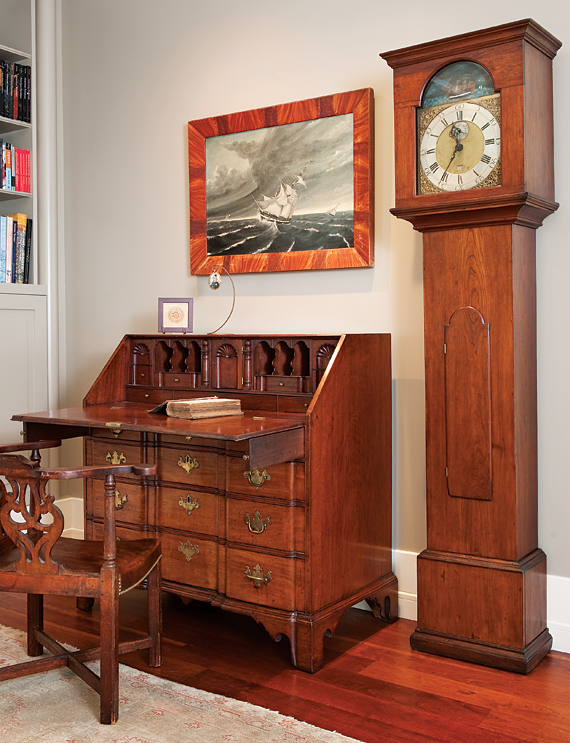 "William Coffin's Ship in a Storm (1846) in its original grain painted frame hangs in the husband's study. Acquired in 1999, it was the couple's first American folk art purchase, and appears on the frontispiece of Robert Bishop's Folk Painters of America (1979). The Chippendale blockfront desk from the North Shore of Massachusetts has a three-shell interior and original brasses. It descended in the family of Nathaniel Bowditch (1773-1838), author of The New American Practical Navigator (1802); a first edition copy of which rests in the desk interior.   In the husband's industry he is looking for the next generation of innovation, but his respect is deep for what was done in the past. The tall clock beside the desk is attributed to Benjamin Cheney of Hartford, ca.1780-1790, and illustrates the husband's interest in clocks. ""The notion,"" he says, ""that clocks reflect the highest level of technological innovation in their period fascinates me; they were cutting edge"" Its cherry case houses a complex wooden works movement with a rare carved rocking ship mechanism. This is possibly the only known American wooden works clock with this feature. While most wooden works have ""30 hour"" movements, this example runs for only 14 to 16 hours, indicating that the maker had not worked out the proper gear relationships required."