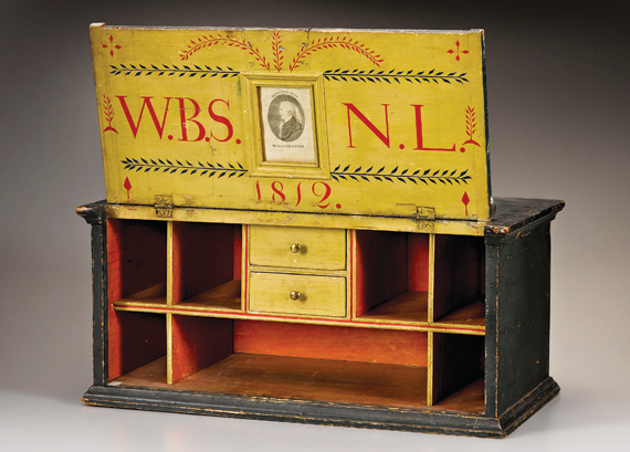 "Washington Benevolent Society traveling desk box, probably Mass., 1812. Pine, original iron hinges, iron lock, brass drawer knobs, molded brass oval pull on top, brass escutcheon, original painted decoration, initialed and dated in red paint ""W.B.S."" ""1812"" and ""N.L.,"" with an engraving of George Washington under glass. H. 10-1/4, W. 22, D. 10-3/4 in."