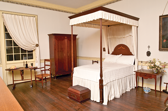 Fig. 5: The Louisiana Federal Bedchamber of The New Orleans Museum of Art represents the only public installation devoted solely to Louisiana-made decorative arts; photography by Terry Thibeau. Oval tilt-top poplar table, ca. 1800–1820. H. 43-3/4, W. 30-3/8 in, L 46-3/4 in. Formerly in the Kuntz collection and now in the collection of the New Orleans Museum of Art (78.206). See also a mahogany armoire, ca. 1815, with stop-fluted stiles and door divider (78.200); a swag-and-tassel inlaid arched headboard on a Federal style walnut highpost bedstead, ca. 1815; and a cherry and cypress wood cabriole leg table, ca. 1800.