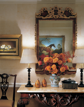 Interior designer Ellie Cullman used mirrors like this circa-1740 English George II parcel and gilt example that's over a circa-1765 English George III mahogany marble-top console to reflect the artwork. Martin Johnson Heade's (1819–1904) Magnolias is on the left.