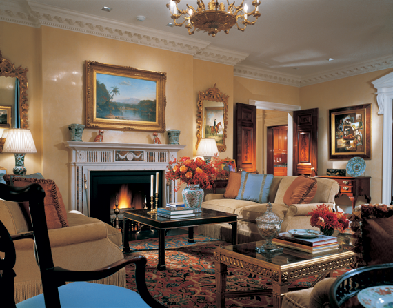 In the living room, Regency style architectural details and light-color Venetian stucco walls make the art, which includes Frederic Edwin Church's (1826–1900) 1857 View of the Magdalena River over the fireplace, stand out. John F. Peto's (1854–1907) 1886 Patch Painting is on the right.