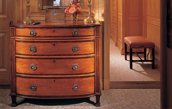 In the collector's dressing room, a circa-1790 George III Sheraton satinwood bowfront chest with rosewood crossbanding and bellflower inlays is mated with a circa-1810 English Regency carved giltwood mirror that's crowned by a stylized bird. Charles Towne's (1781–1854) 1827 Hunter in a Landscape hangs over a circa-1770 George III mahogany footstool.