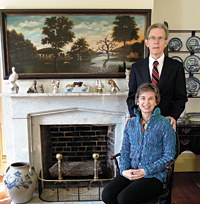 Scholars Leslie and Peter Warwick in front of one of their favorite objects, an overmantel by Winthrop Chandler (1747–1790).