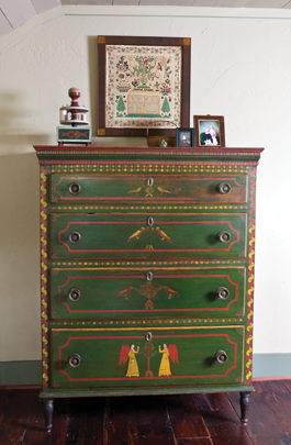 "The Mahantongo Valley chest was in the collection  of Henry Reed, author of Decorated Furniture of the Mahantongo Valley (1987). While the color palette of green with red and yellow detailing is distinctive to the region, the presence of painted birds and angels is among the rarer combinations. ""I love the small items,"" says the wife, referring to such objects in the collection as the sewing box and Nantucket basket seen here. ""I find them the most intriguing."" The portrait miniature of a child from the Orne family of Salem, Massachusetts, is one of the couple's most recent acquisitions. The double portrait is by Mrs. Moses B. Russell. The sampler, worked by schoolgirl Harriet Arnold, is dated 1828 and has its original ribbon edging. Amy Finkel believes it is one of the best known from Reading, Pennsylvania."