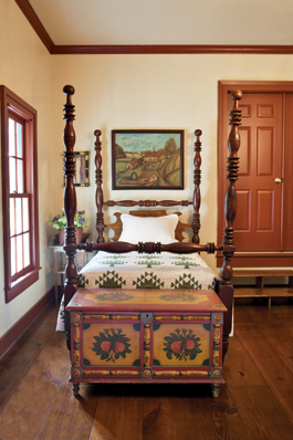 The red- and yellow-painted chest is one of the best of a small group from York County, Pennsylvania. Though most of the furnishings in the collection are from Pennsylvania, the couple was delighted to locate this bedstead, made in Burton, Texas. The 1909 farm portrait by F. P. Bodwell represent's the artists home in New York State as it appeared in the 1830s. A legend on the reverse identifies elements in the work. The washstand is a visual delight, with faux graining, dots, and swirls.