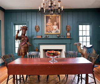 "Painted fancy chairs are set around the original red-painted, circa-1820–1840 harvest table, which dealer Marguerite Riordon used in the dining room of her home. The circa-1840–1860 portrait of two young boys hangs above the mantel, on which there is a paint-decorated box, Schimmel eaglet, and carved dog and pigeon. The carver of the Indian trade figure worked for Samuel Robb (1851–1928), whose influence is evident in the treatment of the feathers, the forward motion of the arm, and the attire, which ""hangs"" longer in the back. The couple's grandchildren have named the figure ""Buttercup."" The camel is attributed to carver Charles Looff (1852–1918), the earliest carousel carver on Coney Island, New York."