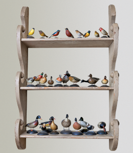 "Seeming to have flocked to the decorative shelf, this group of carved birds are all by renowned decoy carver Elmer Crowell (1862–1952) of East Harwich, Massachusetts; the birds were acquired from Russ and Karen Goldberger. The husband notes, ""We like decoys but their size was impractical so we prefer the miniatures; they are much more manageable."""