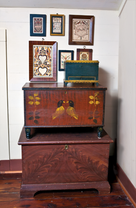 The stacking of chests is done for aesthetics as well  as to save space. From the largest to the smallest, they are from Preystown, Pennsylvania; Virginia; and New England, respectively. The fraktur on the wall consist  of bookplates, family records, birth and baptismal certificates.