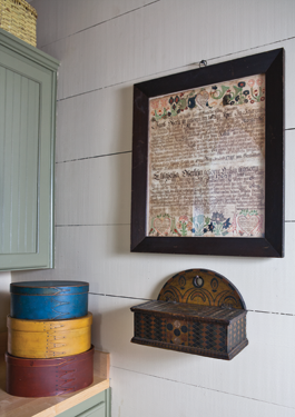 "The kitchen is simply decorated. In one corner, a 1786 marriage certificate hangs above a circa-1820–1850 carved and painted hanging box from Somerset County, Pennsylvania. Three stacked and painted boxes are showing their ""swallowtail"" joints distinctive to the Shakers."