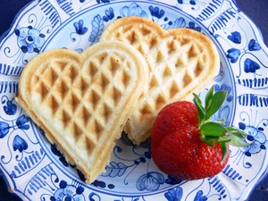 Plate with two waffle hearts and strawberry