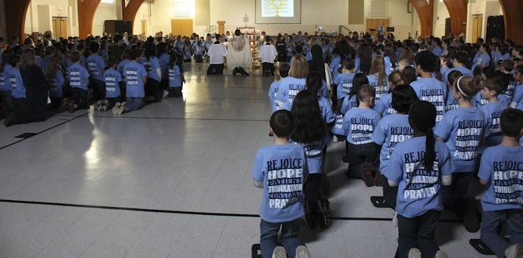 Adoration Fr. Perez kneeling cropped
