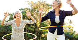 two women laughing with hula hoops, happy and healthy
