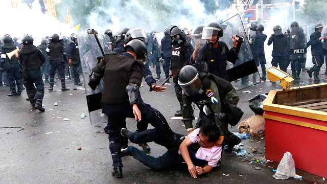 Thai policemen kick an anti-government protester