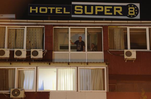 People look from the window of a quarantined hotel in Skopje
