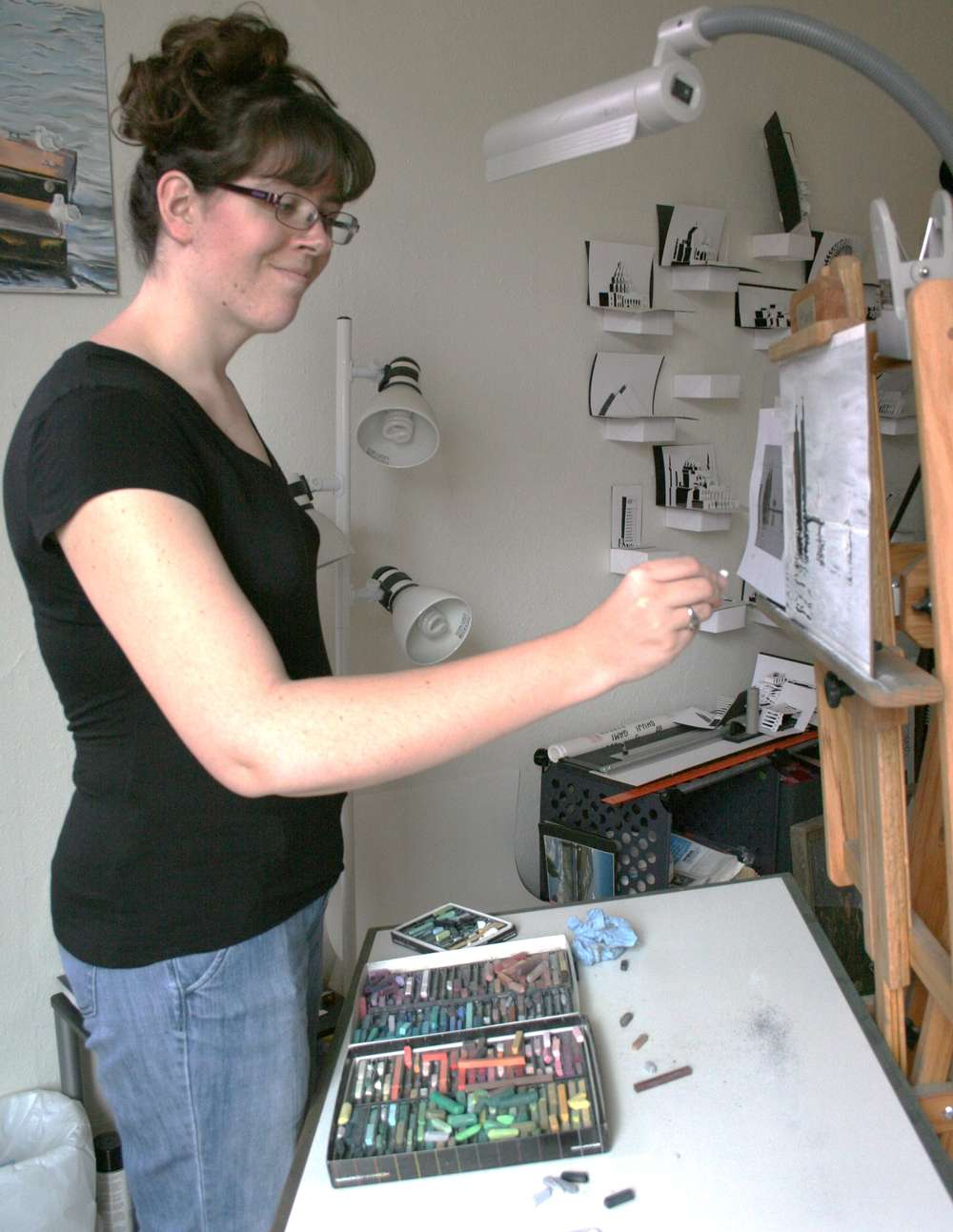 Photo of the artist happily drawing at her easel.