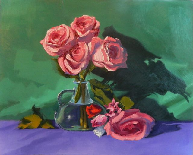 four pink roses against a forest green backdrop and on a violet fabric table cloth