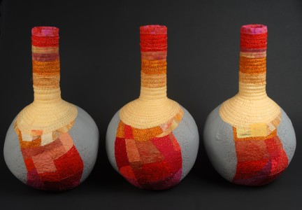 Three beaker shaped fiber vessels in reds and oranges