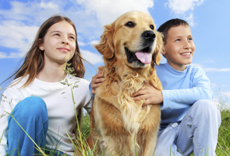 Young boy and girl sitting in grass with dog