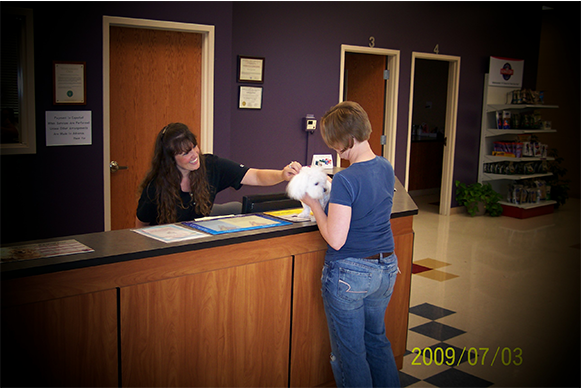 Gina greeting a white dog and its owner at the front desk
