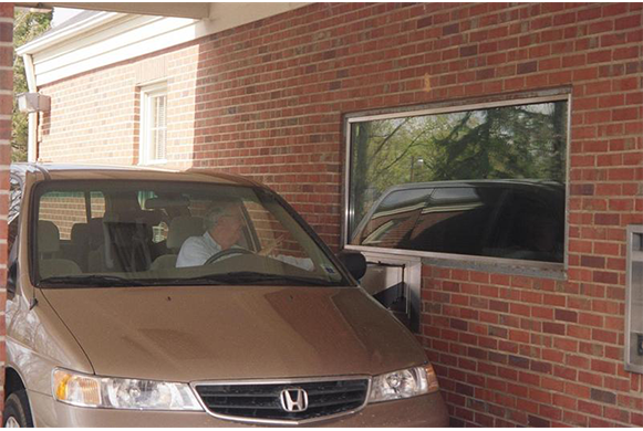 Client receiving their prescription medicine through the drive-thru window.