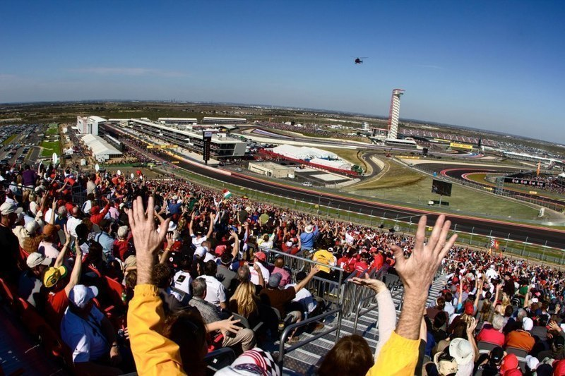Formula-one-us-grand-prix-track-austin-texas-trackside-east-turn-1-view-of-track-and-main-stretch-fans-cheering-helicopter-circuit-of-the-americas-experiences