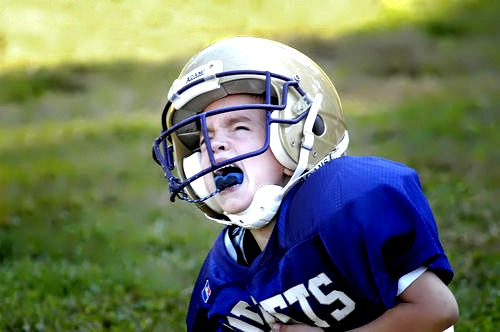 Child playing football hurt, crying
