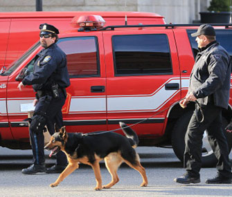 A dog helps police in Boston with their investigation after two explosions went off near the finish line of the Boston Marathon on Monday.