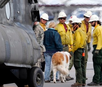 A flood victim and her dog are helped off of a helicopter at the Boulder Municipal Airport in Colorado after being rescued on Monday.