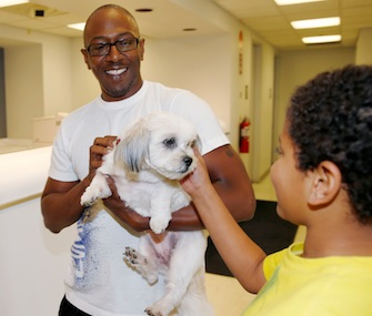 Kelly Booker and his son, Azzah, were reunited with their Shih Tzu, Lilly, Thursday.