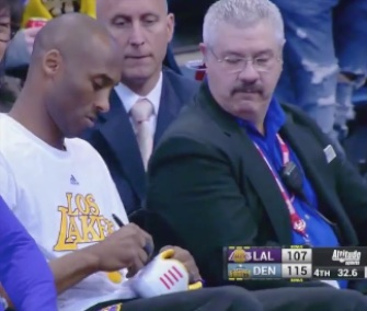Lakers star Kobe Bryant signs his shoes for young fans who guessed his dog's name.