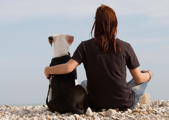woman with arm around dog at beach