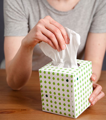 Woman grabbing tissue out of box