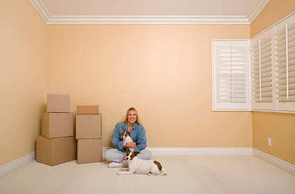 Woman with dogs in room with moving boxes