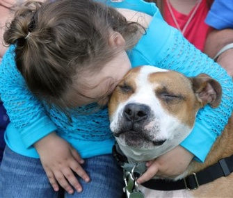Kelsey James, 10, hugs Reckless, who was found at a shelter a year and a half after he disappeared during Superstorm Sandy.