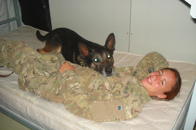 Air Force Staff Sergeant Christine Campos relaxes on her cot with her dog, Bico F544