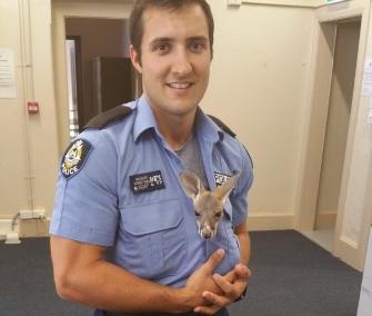 Cuejo cuddles with his hero, Cue, Australia, Police Constable Scott Mason.
