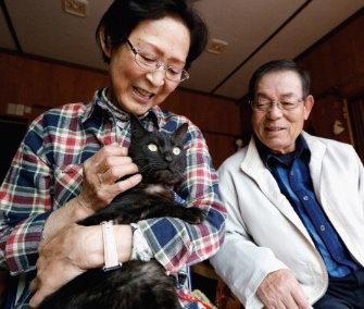 Kazuko, left, and Takeo Yamagishi are reunited with their cat, Suika, in Japan.