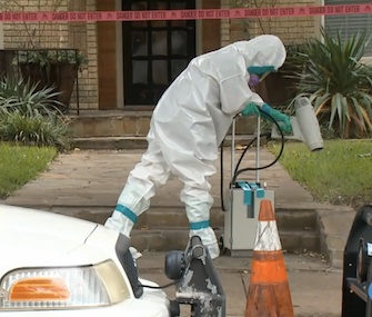 Workers clean outside the Dallas apartment building of a health care worker who tested positive for Ebola.