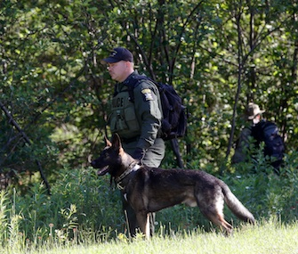 A law enforcement officer and dog search for escaped prisoners Richard Matt and David Sweat in New York last week.